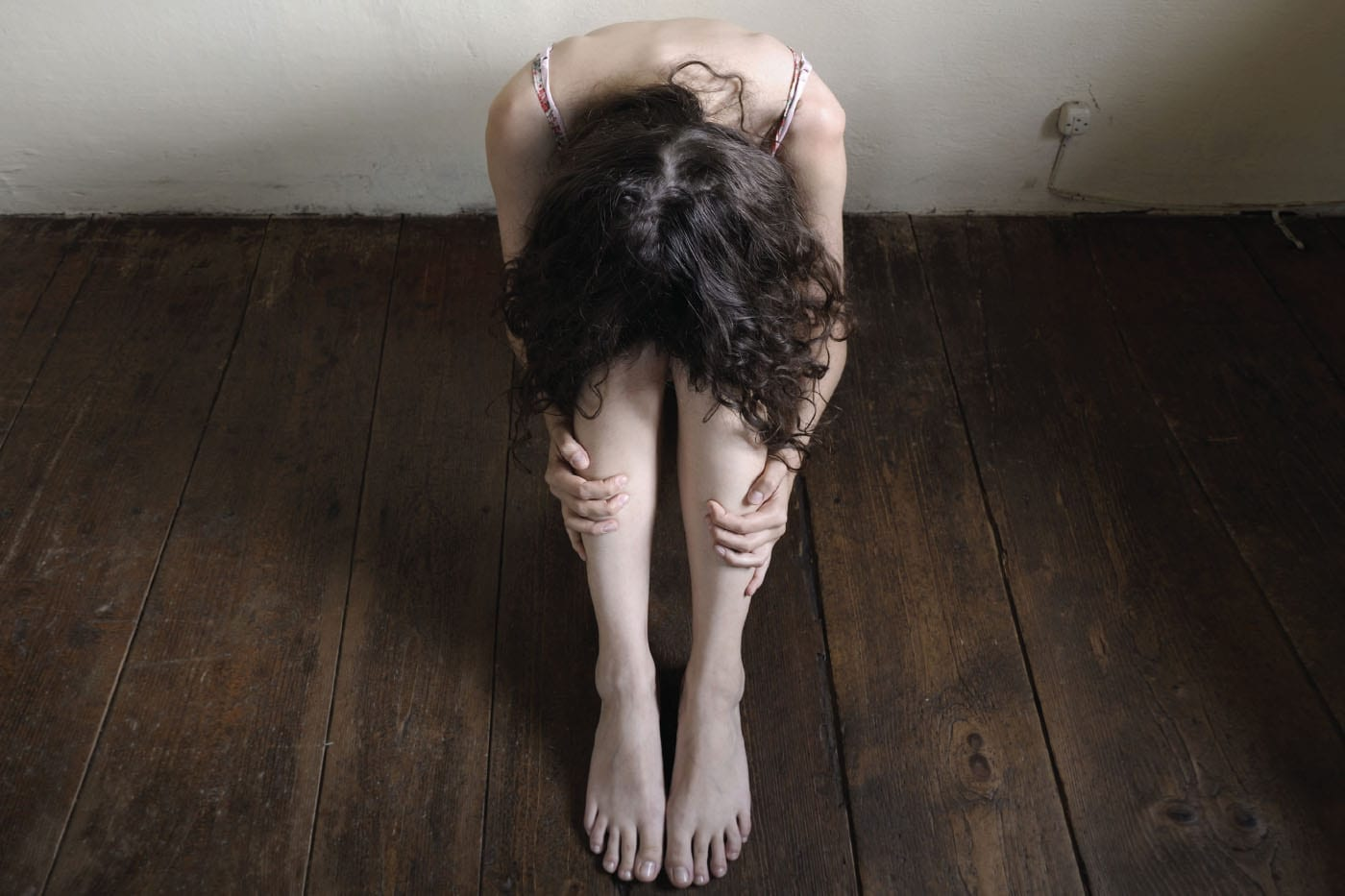 The Face of Human Trafficking - Woman Hunched Over